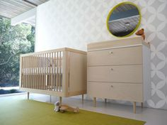 Light natural wood crib and matching changing table with dresser stand beneath patterned white and grey wall with yellow framed mirror in this nursery, with floor to ceiling glass on exterior wall.