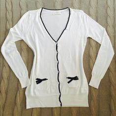 Bow Cardigan Bow Cardigan  NWT White with black accents Functional pockets with bows on front Button up front  2 Small 2 Medium 2 Large available **Tags on actual item are not correct. Size tags say XL and larger, but actual sizes are equivalent to S, M, L**  ⭐️Please do not purchase this listing. Comment and I will make a separate listing for purchase⭐️  Trades PayPal ⭐️Price is firm⭐️ Sweaters Cardigans