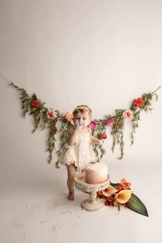 SugaShoc Photography Baby Photographer Bucks County PA Doylestown PA Cake Smash Session with Flowers baby standing by ombre cake in cream lace romper with floral garland and fresh flower bouquet boho chic