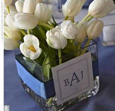 Tables were topped off with white linens and blue table runners and blue napkins atop white chargers. Centerpieces of white tulips in square vases were wrapped with blue ribbon and finished off with the couple's monogram.