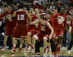 Wisconsin Badgers players celebrate after overtime in the finals of the west regional of the 2014 NCAA Mens Basketball Championship tourname...