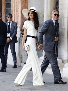 Amal Alamuddin Weds George Clooney wearing Stella McCartney ~The newlyweds shown the civil ceremony in Venice, moments after being officially married September 29, 2014. ~The bride wore a two-piece cream top and trousers with an off-white box clutch, all by Stella McCartney. ~ The long, fluid lines of her trouser suit could earn it a place in fashion and pop-culture history alongside Bianca Jagger's iconic wedding-day pantsuit. The wide-brimmed hat underscores the resemblance.