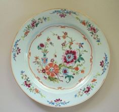 Lovely Antique Chinese Plate with raised enamels in vivid colours with a gold rococo border and a floral border with a blue vase in off center .. well