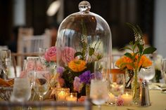 I like the use of the bell jar - a unique way of highlighting the floral centerpiece..it makes you want to see what's inside