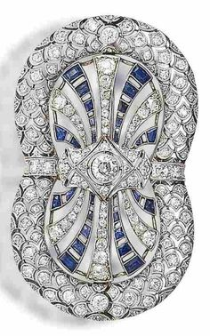 An Art Deco sapphire and diamond brooch, circa 1925. The openwork double horseshoe brooch, with a central old brilliant-cut diamond, pierced geometric surround and fishscale border, set throughout with old brilliant and single-cut diamonds and calibré-cut sapphires, French marks, length 6.0cm, later brooch fitting.