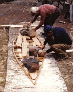 Laying out a sheet of bark for a new birchbark canoe . The gunnels are weighted on the birchbark sheet ...the bark is  then bent up along the sides into the shape of the canoe ; from ''Building an Algonquin Birchbark Canoe '' ; photo Henri Vaillancourt ; Maniwaki, Quebec , 1980