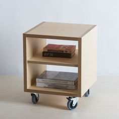 Simple plywood bedside cabinet with shelf on lockable castors