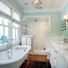 Pretty colors and bathtub! Shows me that the modern glass shower can look good in a vintage bathroom, especially with a chandelier and aqua walls!