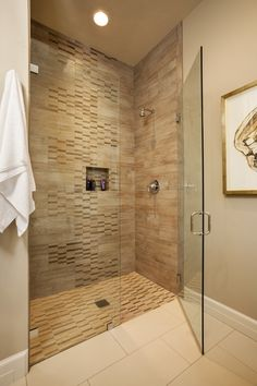 he guest bathroom has a stone tile shower with a glass door. The bathroom is in a warm neutral beige.