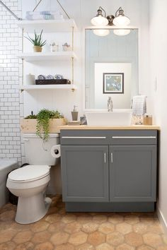 Nice bathroom idea. Honeycomb floor tile, white wall tile, open white shelves and grey cabinets.