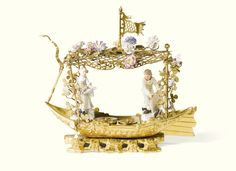 A Meissen porcelain-mounted gilt-bronze inkstand the porcelain circa 1750-55 in a form of a boat covered by a trelliswork pergola surmounted by a flag and mounted with porcelain flowers enclosing two Meissen figures depicting a fishseller and a fisherwoman, with a receptacle for inkpot and sander and writing implements on a rockwork and brickwork base Sotheby's