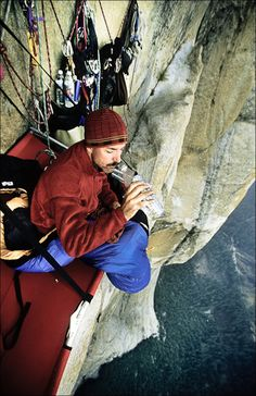 Kevin Brown drinks water on his hanging cot near the end of a multi-day ascent of El Capitan in Yosemite Valley, California.  Great Photo perspective for a great climbing achievement