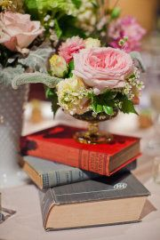 Centerpieces with stacks of vintage books topped with small bouquet in crystal / glass sherbet