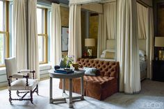 In the master bedroom, the bed canopy and curtains are of a Lulu DK linen, and the silk rug is by Beauvais Carpets; a custom-made settee upholstered in a Clarence House velvet faces a marble-top Directoire table and a 19th-century spool-leg chair.