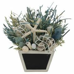 """Artful on its own or anchoring a beach-chic vignette, this eye-catching basket showcases avena, turquoise grass, and assorted shells. Use the chalkboard planter to pen reminders and welcome notes.   Product: Faux floral arrangementConstruction Material: Avena, grass, shell, burlap and woodColor: BlueFeatures:  Includes natural grasses and shellsChalk-board baseDimensions: 11"""" H x 10"""" W x 9"""" D"""