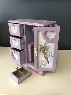 This vintage jewelry box has been painted a pastel purple and sealed with a polycrylic finish. The doors and drawers have been decoupaged with a whimsical fairy print. The door opens to a mirror backing, a necklace carousel and a ring pillow. There are three drawers on the left
