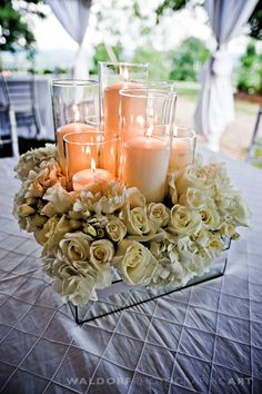 Mirrored cube vase centerpiece with lots of candlelight and cream spray roses. Modern, formal, minimalist, elegant flowers.