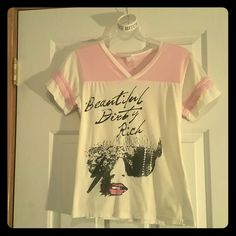 """BUNDLE Lady Gaga Gear! Calling all Lady Gaga fans! This bundle makes a great addition to any little monster's closet ;) Gently worn, vintage looking, off white and soft pink tee features the song title """"Beautiful Dirty Rich."""" Size L but fits more like a smaller M. Also, a white and silver rubber bracelet that features the lyrics, """"I'm A Free Bitch."""" The silver in the letters is a bit worn in some spots, but I think it adds to its edgy look. Bundle this 2-piece listing for savings on top of…"""