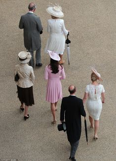 love the hats - ah to be a princess! Prince Charles (top left) and the Duchess of Cornwall, the Duchess of Cambridge in pink walk to meet guests at the Buckingham Palace garden party