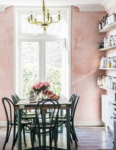 Feminine dining space with pink walls, a gold chandelier, and a vintage dining table