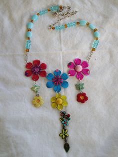 Necklace with 3 large flowers as focal piece, 3 smaller flowers hang from each flower with a butterfly and bee. Chain is an assortment of blue and amber glass bead with silver chain. FOR SALE .. SHIPPING IS INCLUDED IN COST .. $35.00