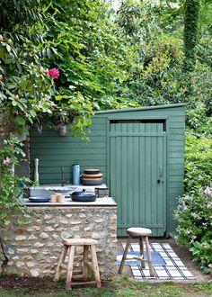 Créez une cuisine américaine dans votre jardin à l'aide de deux murets parallèles en pierre en équipant l'un d'eux d'un évier. Le second muret fera office de bar ou de plan de travail pour préparer les repas. Il ne manque plus qu'un barbecue et les éléments telle que la cabane à peindre d'une couleur verte. Le tour est joué pour posséder une cuisine d'extérieure en harmonie avec l'environnement dans lequel elle se trouve.(c) Marie-Claire Maison