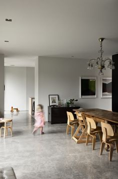 """The 1920s Catalan chandelier and dining room table were both bought second-hand from a shop in Barcelona, where the family used to live. The table is the perfect place for the children to draw and play, """"because it's so old it doesn't matter if it gets scratched,"""" says Bergendy. """"It's technically a dining room with old-style wood panels, but the treatment is new — it's not cutting edge, but the way the materials have been treated is different."""""""
