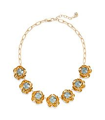 Feminine, sculptural and vintage-inspired — Tory Burch Crystal Rose Necklace's floral charms pair faceted blue glass stones with antiqued gold, a rich combination that works for day or evening. The chain can be adjusted to suit a variety of neckline styles. It's a versatile statement piece that adds a touch of romance to any look.