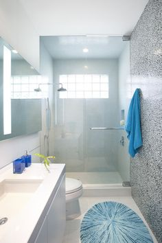 Bathroom design for a smaller bathroom. Bright and colorful focal wall, white and clean, large window to provide natural sunlight and colorful accents.