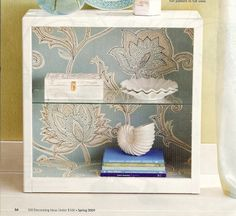 Transform the drab into the fab by backing an ordinary bookshelf with wallpaper and replacing the wood shelves with glass.