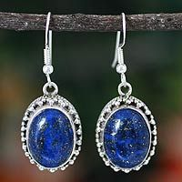 Lapis lazuli emanates a deep blue mystique, showcased in argent settings. Surrounded by a halo of silver, the elegant stones grace handcrafted earrings by Shanker.