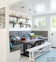 Stretched across every inch of spare wall, this U-shape banquette maximizes both seating and table space. A long bench placed on the empty side of the table was painted white, allowing it to blend with the floor and the base of the banquette. Storage drawers beneath the bench provide spots to stow away table linens, serving platters, and other dining odds and ends./