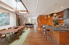 This Bond Street penthouse has hardwood flooring, a simple area rug, stone countertop, oval dining table, large skylight, wood paneled walls, an open spiral staircase, and a charming terrace.