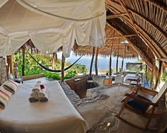 hut on the sea with drapes, stone floor and bamboo ceiling. Like escaping into the Swiss Family Robinson.
