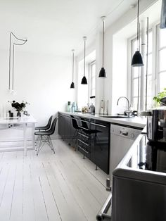 Black cabinets, white floor and huge windows.