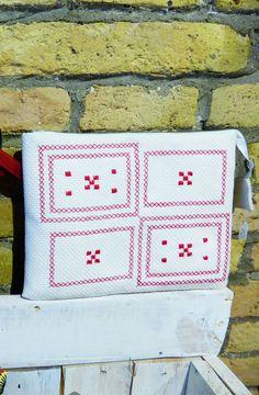 Bolso de mano blanco con bordado en punto de cruz rojo, que puede convertirse en estuche para guardar la tablet.