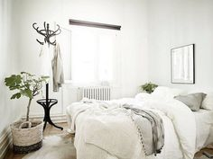 Classic black coat stand in the corner of the bedroom in a Swedish space in…