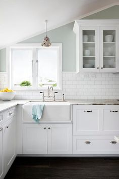 Stunning kitchen features white cabinets paired with Fantasy Brown Granite countertops in a leather finish alongside half the wall clad in subway tiles and the other half painted robin egg's blue. A farmhouse sink by Acquello is paired with a deck-mount hook and spout faucet by Perrin & Rowe placed under window and a sloped ceiling.