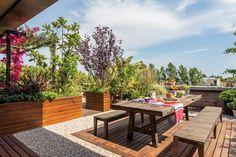 """Ideas para darle vida tu patio o balcón. Con una superficie de casi 200m2, esta terraza aporta una magnífica dosis de verde y aire libre. El diseño de este espacio corrió por cuenta de Nicolás Rodríguez, del Estudio Paisaje. """"Queríamos un jardín en altura que fuera variado y tuviera ejemplares de árboles, además de arbustos y plantas"""". Sobre el deck de incienso, la parte más social de la terraza con un juego de comedor en pino tea."""