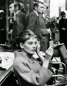 Audrey Hepburn fixing her makeup on the set of Breakfast at Tiffany's.