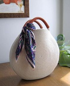 Round white bag made out of cotton rope and up-cycled soft brown leather. This bag is durable and roomy enough to fit all your necessities - measures about 12 inches across and 2 inches deep, with about 3 inch handles. Find a simple cotton rope basket bag Crochet Handbags, Crochet Purses, Round Basket, Basket Bag, Denim Bag, Cotton Rope, Knitted Bags, Handmade Bags, Leather Handle