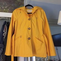 MICHAEL KORS Yellow Raincoat/Trench A super sophisticated and classic piece from Michael Kors. Yellow raincoat/trench coat with tortoise buttons and silver details. Has pockets and optional waist belt with Michael Kors engraving on silver belt buckle. There is a small stain on the edge of the left sleeve and the color as pictured. They will most likely come out with washing. Feel free to ask questions/more pictures! Size XS, but I am size S-M and this jacket is only slightly right across the…