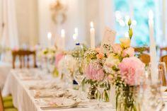 Für die Gäste der Hochzeit wurden in dem Saal lange Tafeln hergerichtet, welche mit Kerzen und Blumen in kleinen Gläsern dekoriert wurden