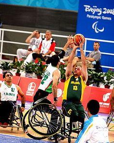 Um atleta tenta arremessar uma bola, enquanto um adversário estica o braço, tentando interceptá-la.