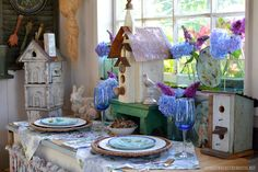Tabletop vignette in the Potting Shed with birdhouses, bunnies, majolica plates and hydrangeas in mason jars | homeiswheretheboatis.net
