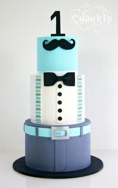 3 tier 1st birthday cake, decorated in a suit. With sugarpaste moustache, bowtie and belt.
