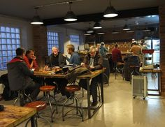 Comfortable stools, solid tables, polished floor, large heated space with bar at far end - Mondo Brewing Co