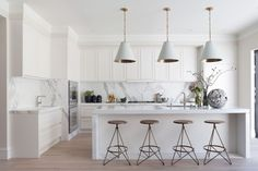 White kitchen with marble tile backsplash and white pendant lights