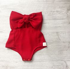 Bright holiday red gives this baby girl romper a festive look. This simple solid red romper can be used for more than just Valentines Day and Christmas. Such a classic look, perfect for Christmas pics or a family holiday gathering! The romper has elastic for a comfortable fit, snap buttons for easy access.