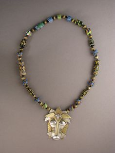 by Ahlene Welsh | Handcrafted 'African Mask' from sterling silver, brass and nickel, that has then been combined with vintage African glass Trade Beads and brass beads from West Africa